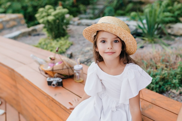 Little tanned lady in vintage straw hat sitting on wooden bench with basket for picnic and camera. outdoor portrait of dark-eyed girl wears white dress posing