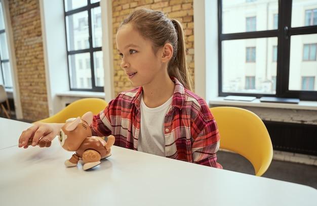 기술 장난감을 가지고 노는 테이블에 앉아있는 동안 옆으로 웃고있는 작은 기술자 귀여운 소녀