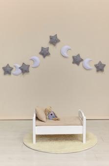 白い木製のdoolのおもちゃのベッドの上の小さなテディベア子供部屋の枕と