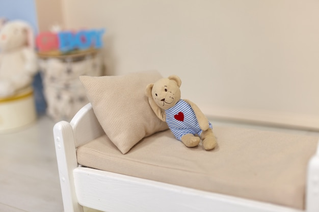 Маленький плюшевый мишка на игрушечной кровати белая деревянная кукла с подушкой в детской комнате