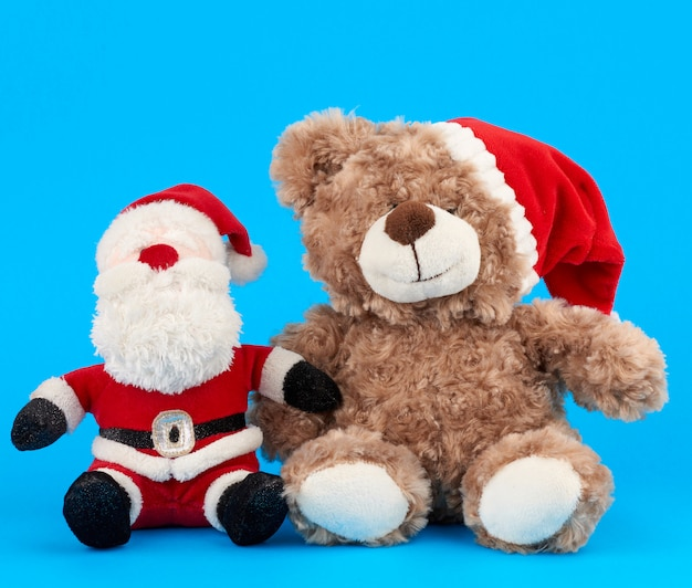 Little teddy bear in red christmas hat and santa claus