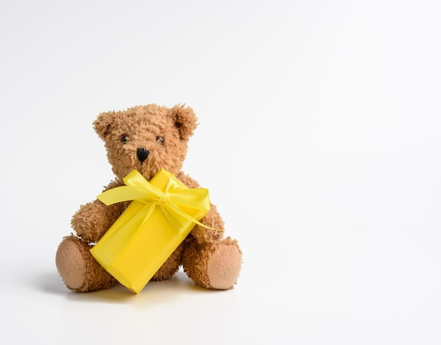 Little teddy bear sits on a white background with a gift wrapped in yellow paper and yellow ribbon, copy space