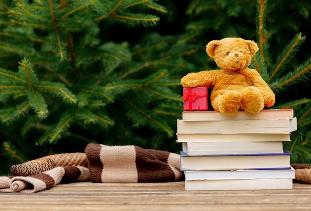 小さなテディベアグッズと背景にトウヒの枝と木製のテーブルの上の本