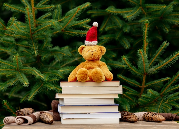 Little teddy bear toy in santa claus hat and books on wooden table with spruce branches on background