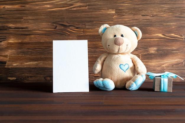 복사 공간이 있는 나무 테이블에 선물 상자가 있는 작은 테디 베어 장난감. 베이비 샤워, 액세서리, 물건, 남자 아이를 위한 선물 1학년 생일, 첫 번째 신생아 파티 배경.