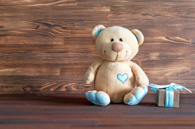 Little teddy bear toy with gift box on wooden table with copy space. baby shower, accessories, stuff, present for boy child first year birthday, newborn party background