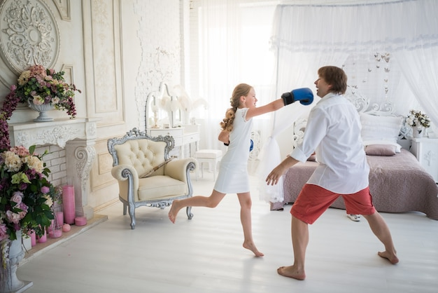 Little teenage girl fights with her dad using boxing gloves while standing in a chic living room with beautiful decor. concept harmful teenagers children parent-child relationship problems