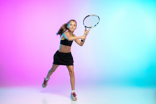 Little tennis girl in black sportwear isolated on gradient background in neon light