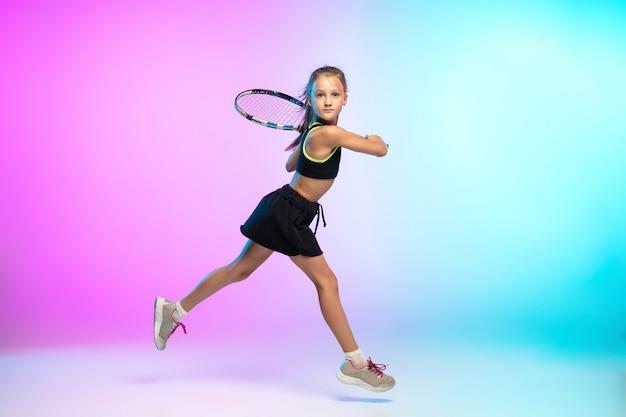 Little tennis girl in black sportwear isolated on gradient wall in neon light