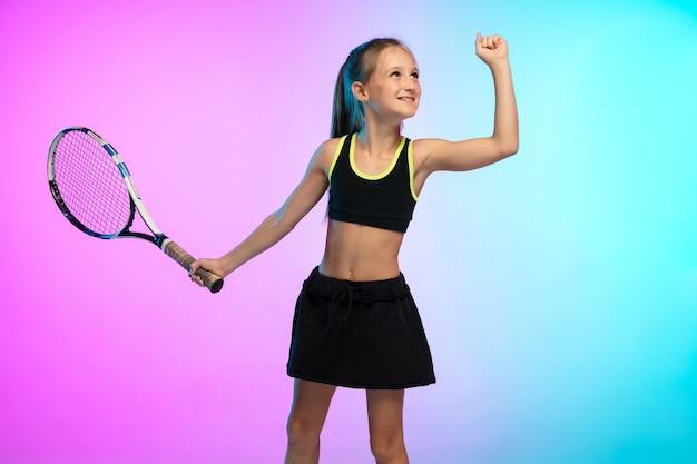 네온 불빛의 그라데이션 벽에 격리된 검은색 운동복을 입은 작은 테니스 소녀