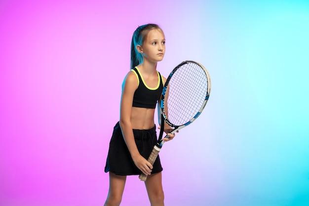 ネオンの光のグラデーションの壁に分離された黒いスポーツウェアの小さなテニスの女の子