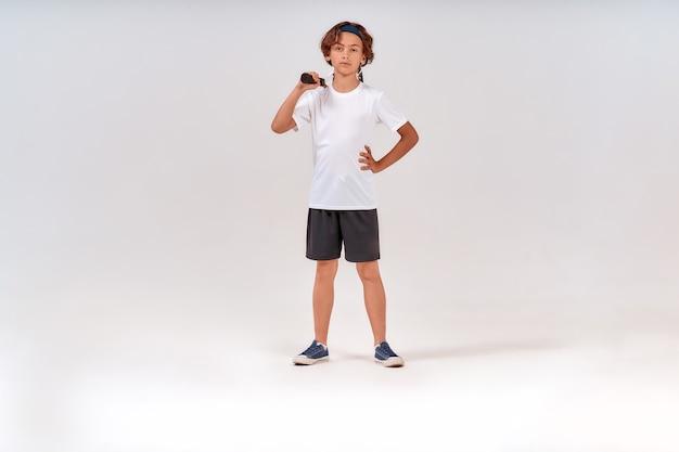 テニスラケットを持って見ている自信を持って10代の少年の小さなテニスプレーヤーのフルレングスショット