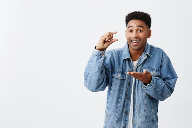 Маленький. крошечный. изолированный портрет молодого красивого смешного счастливого чернокожего человека с афро прической в вскользь джинсовой куртке жестикулируя с руками, смотря в камере с радостным выражением