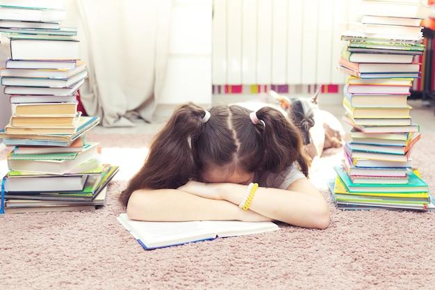 床に横になって読んでいる小さな疲れた白人の女の子。彼女の隣には犬とたくさんの本があります。