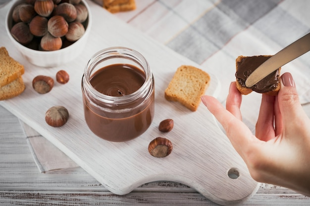 Little toasts with sweet hazelnut chocolate spread for breakfast on white wooden surface. woman's hand holds a knife