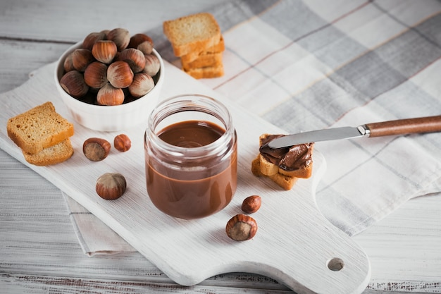 Little toasts with sweet hazelnut chocolate spread for breakfast on white wooden wall