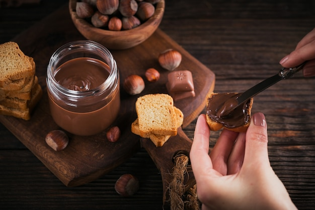 Little toasts with sweet hazelnut chocolate spread for breakfast. woman's hand holds a knife
