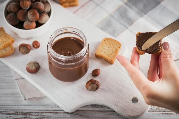 달콤한 헤이즐넛 초콜릿과 함께 작은 토스트는 흰색 나무 표면에 아침 식사를 위해 퍼졌습니다. 여자의 손에 칼을 보유