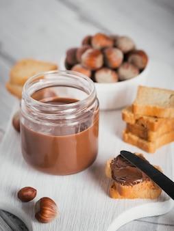 흰색 나무 표면에 아침 식사를 위해 달콤한 헤이즐넛 초콜릿 스프레드와 함께 작은 토스트