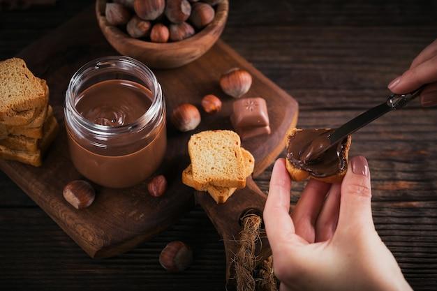 달콤한 헤이즐넛 초콜릿을 곁들인 리틀 토스트가 아침 식사로 퍼졌습니다. 여자의 손에 칼을 보유