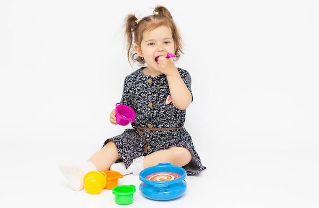 작은 유아 2 세 흰색 배경에 부엌 장난감을 재생