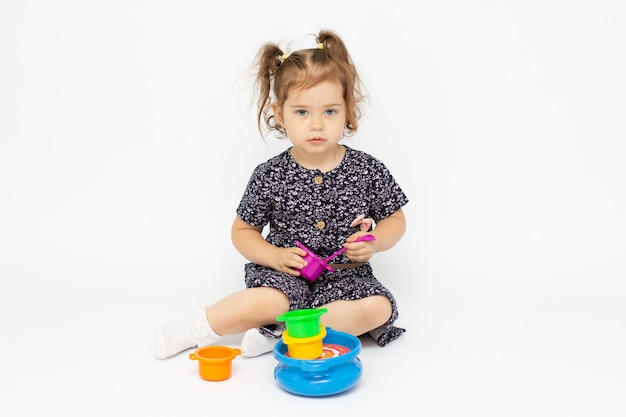 Little toddler 2 years old playing kitchen toy on white background
