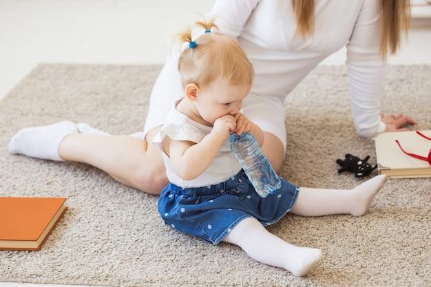 自宅でミネラルウォーターのボトルを持つ小さな幼児の女の赤ちゃん。子供と家族の概念。