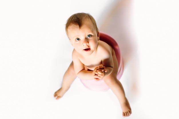 Little toddler baby kid girl sitting on plastic potty on a white background