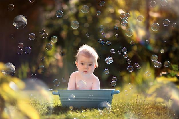石鹸の泡で公園で入浴する小さな幼児男の子