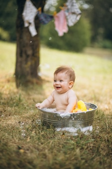 Little toddler boy bathing in park