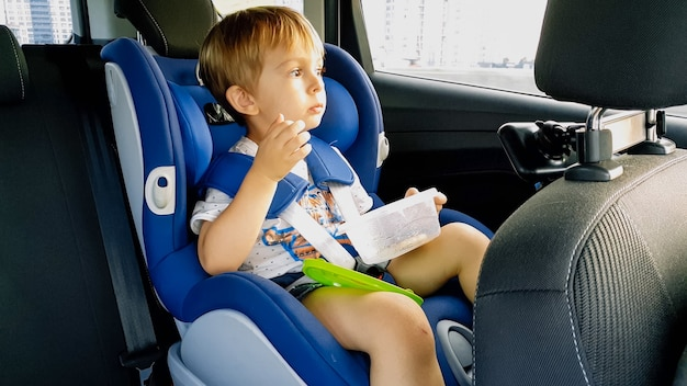 Little toddler boy feeling hungry and eating while travelling by car in child safety seat