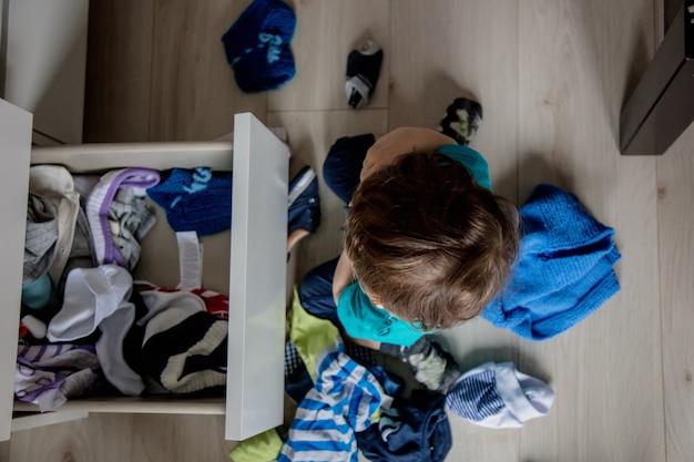 집에서 찬장에서 옷을 가지고 노는 어린 유아 소년