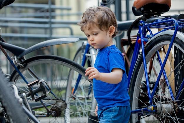 어린 유아 소년은 도시 자전거 주차장에서 큰 자전거로 열정적으로 활약합니다.