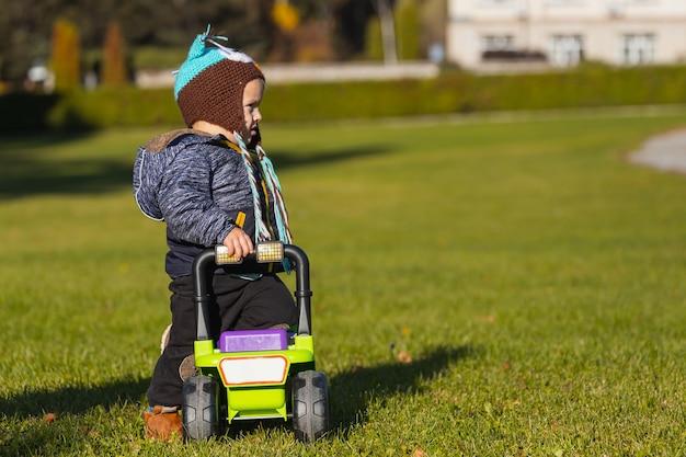 小さな幼児の男の子は、緑の芝生の上に緑のジープ車椅子で公園で遊ぶ