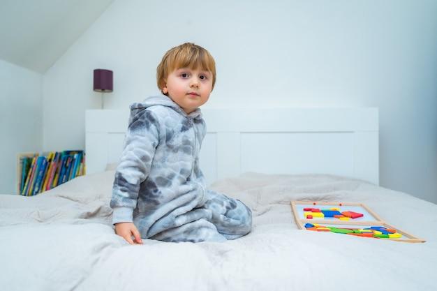 작은 유아 소년 나무 자기 생성자에 침대에서 재생