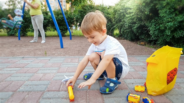 Little toddler boy sitting on the ground at park and playing with toy cars
