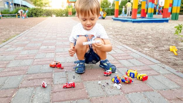 Маленький мальчик-малыш сидит на земле в парке и играет с игрушечными машинками
