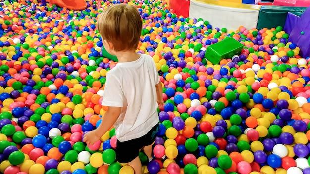Маленький мальчик гуляет и перелезает через множество красочных пластиковых мячей на детской площадке в торговом центре