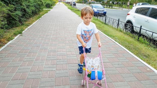小さな幼児の男の子が道を歩き、人形のおもちゃのベビーカーを押す