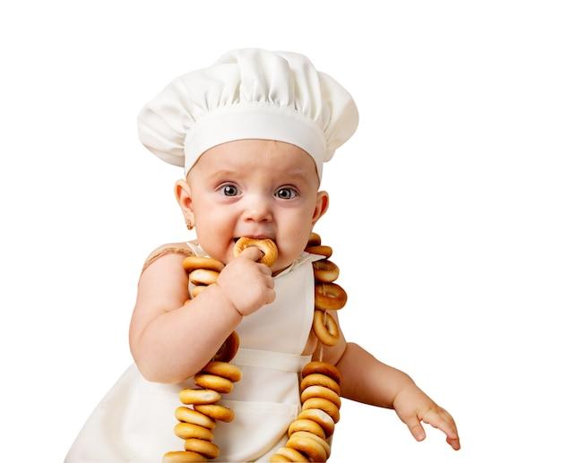Маленькая девочка малыша в костюме шеф-повара ест рогалик. изолированные на белом фоне