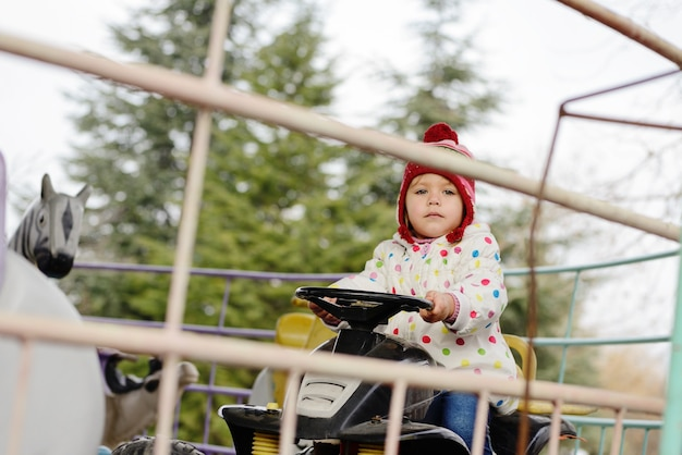 Little toddler girl riding on funny car on roundabout carousel in amusement park