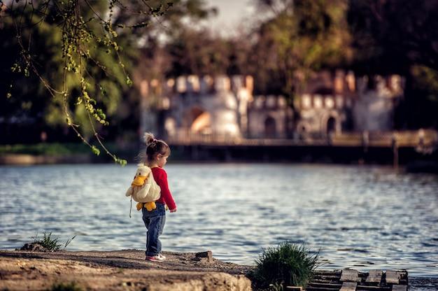 Маленькая девочка-малышка стоит на берегу озера на фоне замка с детским утиным рюкзаком