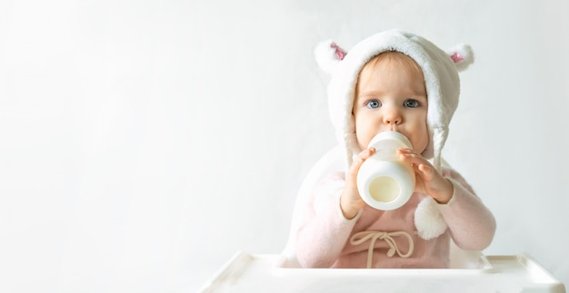 Little toddler girl in a warm fluffy hat drinks milk from a bottle while sitting. gray background