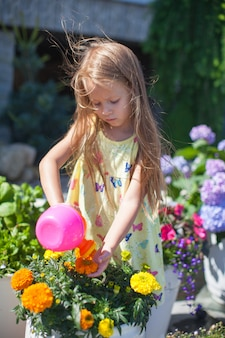 Little toddler girl watering flowers with a watering can
