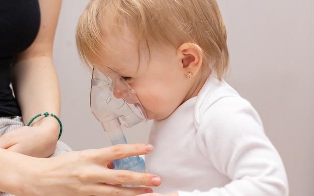 Маленькая девочка-малышка с астмой и аллергией делает ингаляцию в маске с лекарством через небулайзер на сером фоне