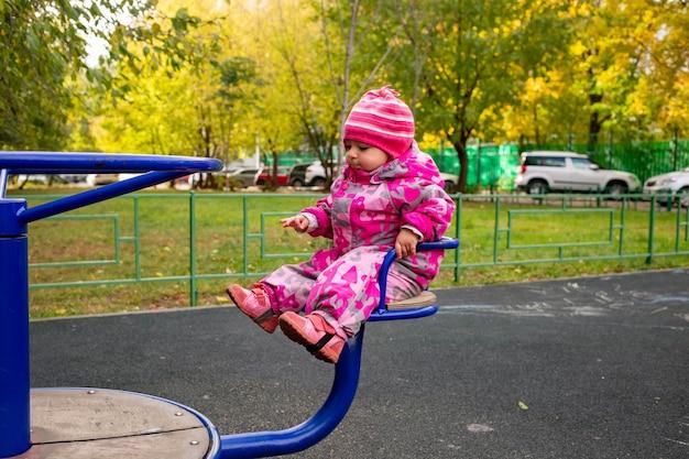 따뜻한 겨울 작업복을 입은 어린 아이가 놀이터에서 놀고 있습니다. 소프트 포커스