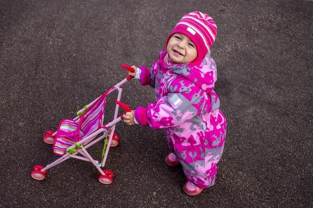 따뜻한 겨울 작업복을 입은 어린 아이가 놀이터에서 놀고 있다