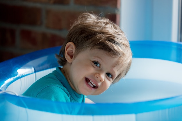 Little toddler is played in an inflatable pool