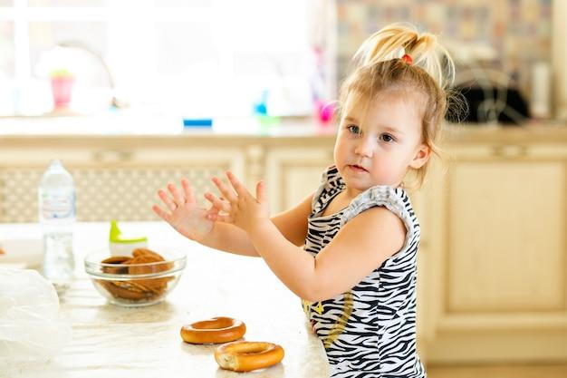暖かい日当たりの良いキッチンで昼食をとっている小さな幼児の子供。 2つのおいしいベーグルで遊ぶ面白いポニーテールのブロンドの女の子。