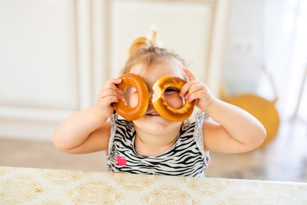 Little toddler kid having lunch in the warm sunny kitchen. blonde girl with funny ponytail playing with two tasty bagels.
